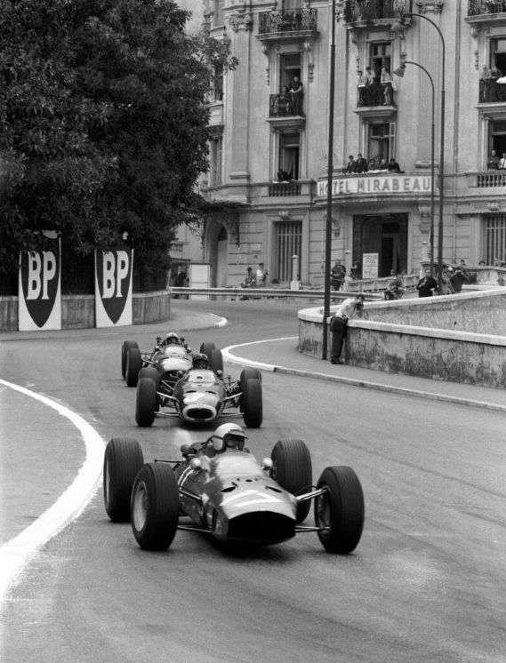Graham Hill, v sevření dvou monopostů Ferrari, vyvíjí tlak na vedoucího Lorenza Bandiniho, Monako, 1965.